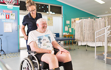 Man pushed in wheelchair by nurse